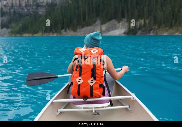 Rear view of mid adult woman with orange colour backpack paddling canoe, Moraine lake, Banff National Park, Alberta - Stock Image