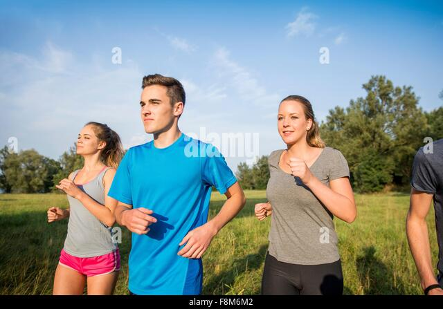Group of friends running through field - Stock Image