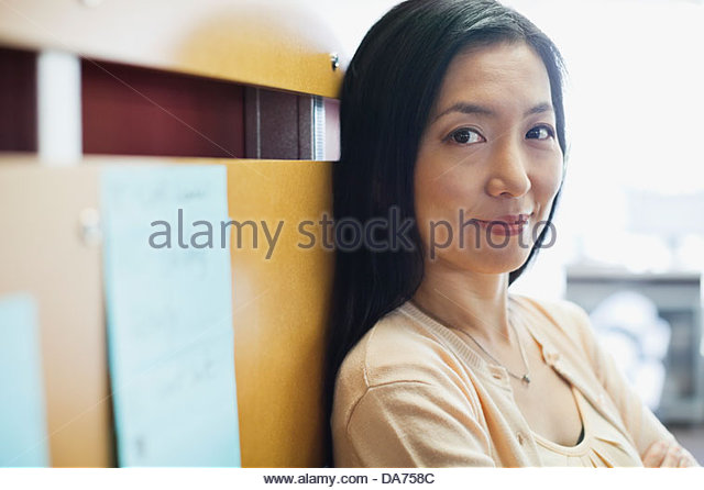 Portrait of businesswoman leaning against wall - Stock Image