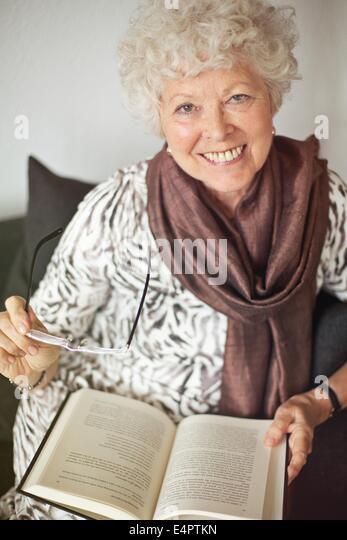 Cheerful mature lady at home enjoying a good book - Stock Image
