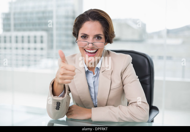 Cheerful businesswoman showing thumb up at her desk - Stock Image