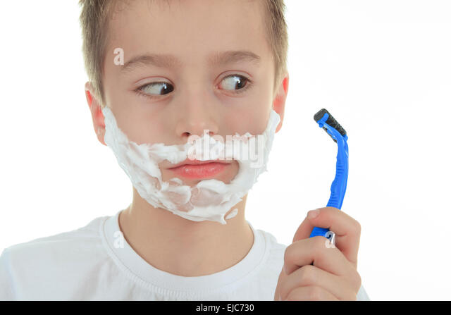 playful little young boy shaving face over white - Stock Image