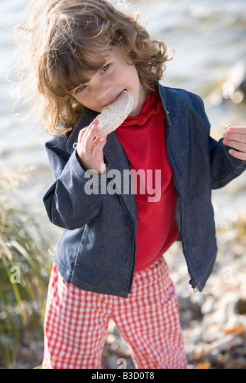 Germany, Bavaria, Ammersee, little girl (3-4) eating bread - Stock Image