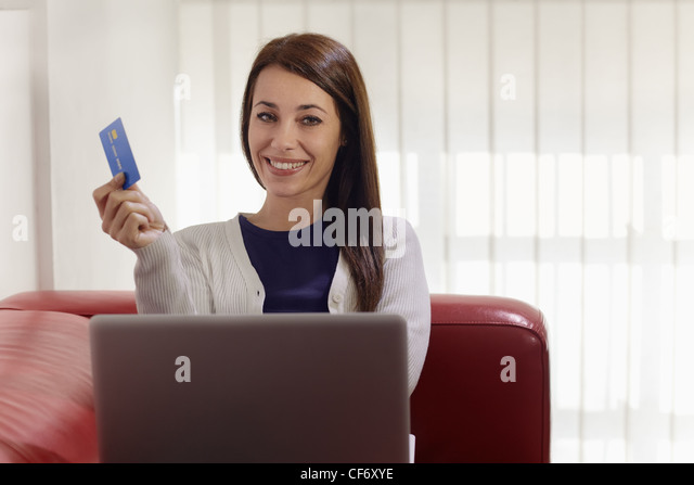 E-commerce with happy woman using pc and credit card while shopping on the web at home - Stock Image