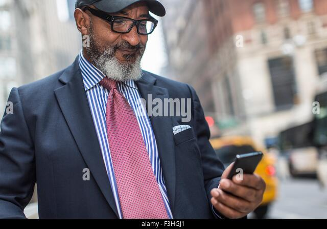 Mature businessman using smartphone on street - Stock Image