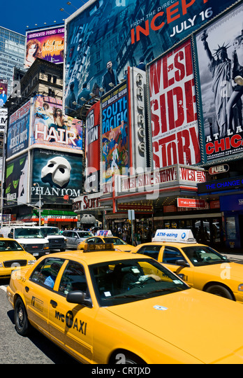 Times Square New York Yellow Taxi, New York City Daytime Broadway Theater Billboards and Yellow Taxis - Stock Image