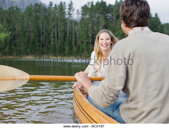 Couple rowing canoe on lake - Stock Image