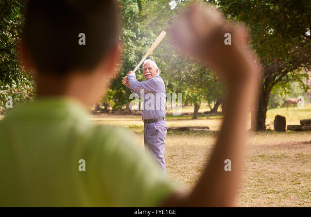 Grandparents spending time with grandson: Senior man playing baseball with his grandson in park. The old man holds - Stock Image