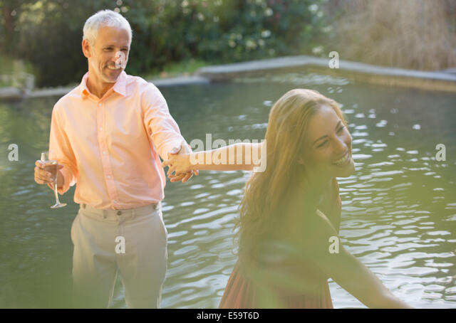 Couple holding hands by pool outdoors - Stock Image