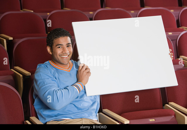 Man sitting in auditorium, holding empty placard - Stock Image