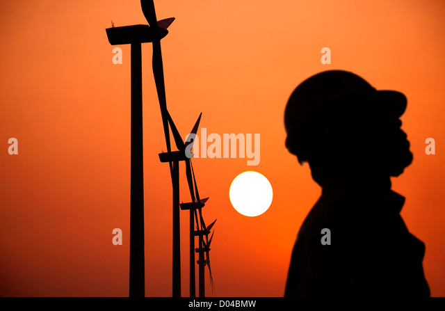 The Silhouette of windmills worker with  sunset - Stock Image