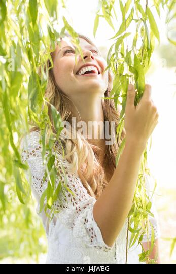 MODEL RELEASED. Young woman touching green leaves. - Stock-Bilder
