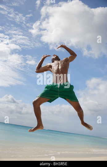 Young man leaping on a tropical beach, smiling - Stock Image