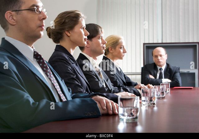 Tense young people are sitting at the table in a line and their displeased boss - Stock Image