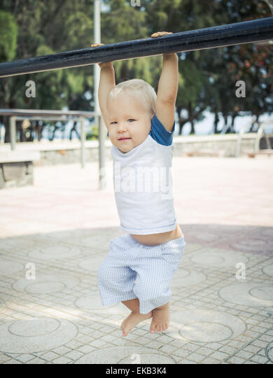 Baby hanging on a pull-up bar - Stock-Bilder