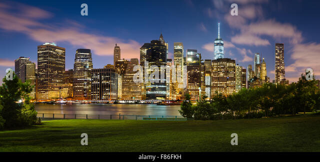 Evening view of Lower Manhattan illuminated skyscrapers across Brooklyn Bridge Park. Manhattan Financial District, - Stock Image