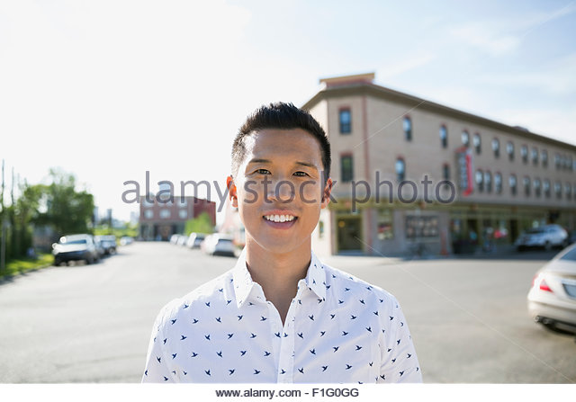 Portrait smiling man in sunny street - Stock Image