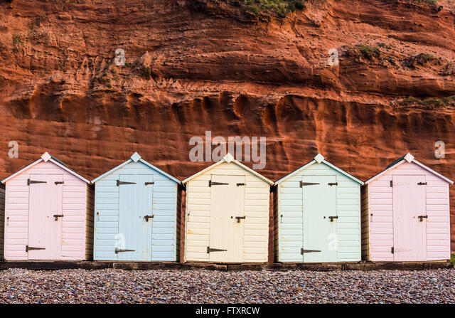 Beach hut row in pastel colors, red rock background, South Devon, UK - Stock Image