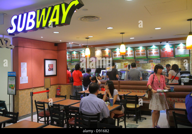 Singapore City Square Mall Subway sandwiches food restaurant tables inside interior Asian man woman - Stock Image
