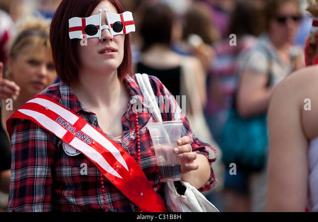 Woman wearing funny sunglasses, celebrating St George's Day at Trafalgar Square, London, England, UK - Stock Image