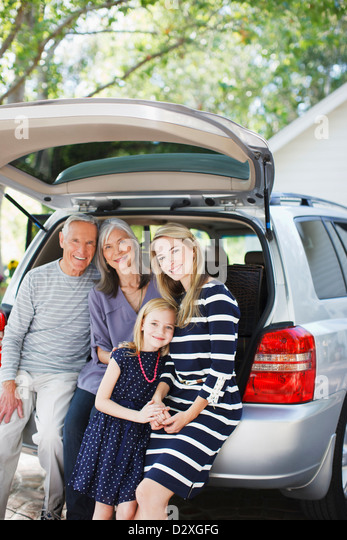 Family sitting in trunk of car - Stock Image