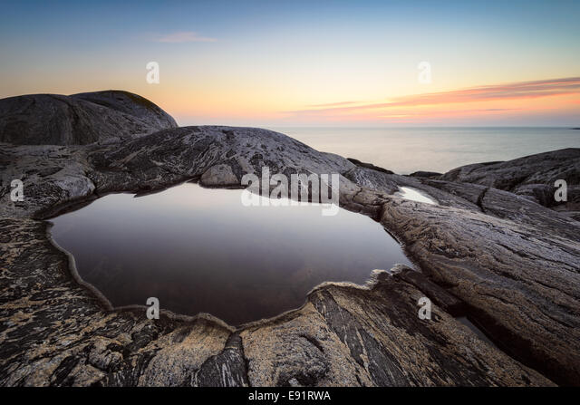 Smooth tide pool surrounded by rock at sunset - Stock Image