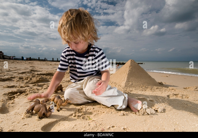 Small boy plays with toy camels at the seaside - Stock Image