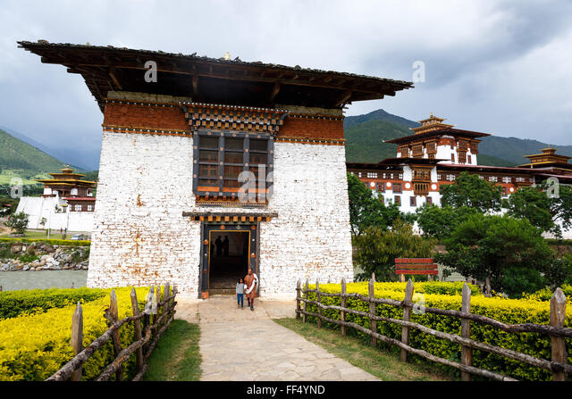 Adult and child stand next to gate of the Punakha Dzong Bridge in Bhutan with Dzong in background - Stock Image