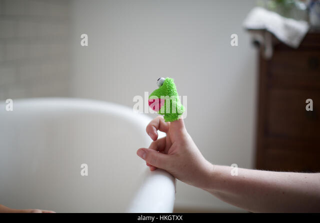 hand with toy animal on edge of the bathtub. childhood, hand, toy, character. - Stock-Bilder