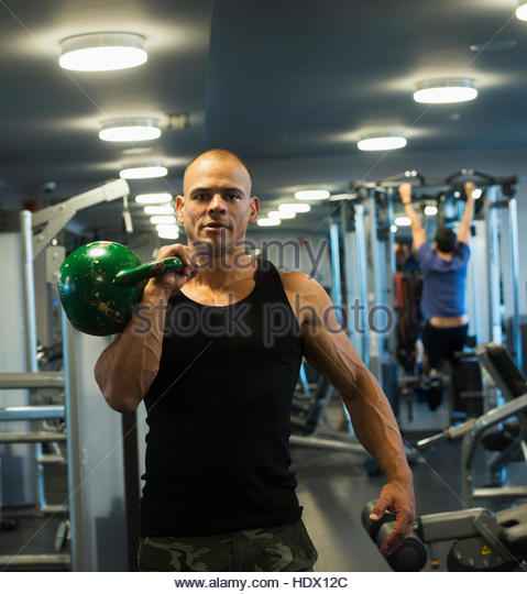 Hispanic man weightlifting with kettlebell in gymnasium - Stock Image