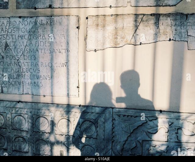 Shadow of a couple on vacation in Rome, Italy, with evening light and fragments of Ancient Rome in Trastevere. - Stock Image
