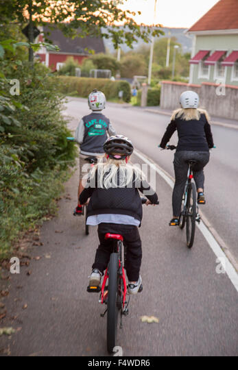 Mother and children (10-11, 12-13) cycling on street - Stock Image