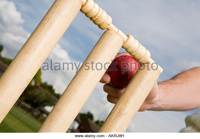 A cricket player touching a cricket stump with ball - Stock Image
