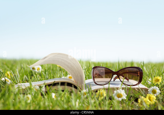 Glasses on a book outside with green grass - Stock Image