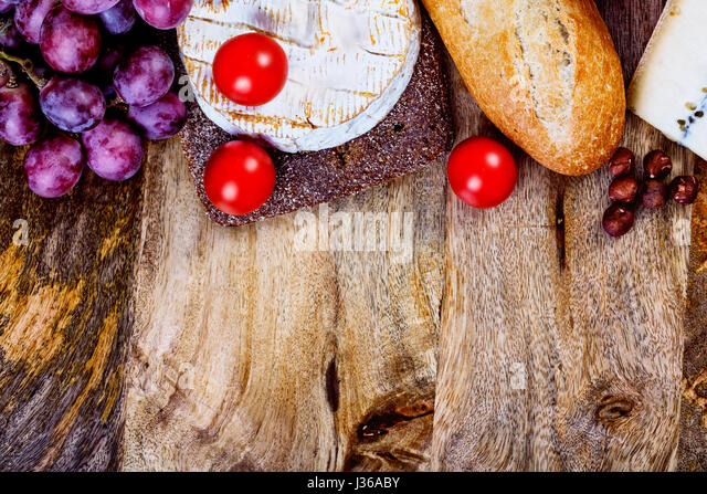 assorted food ingredients - cheese, bread, tomatoes and grapes and vertical copyspace ready to be filled with some - Stock Image