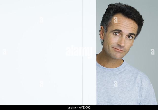 Man looking around corner of wall, portrait - Stock Image