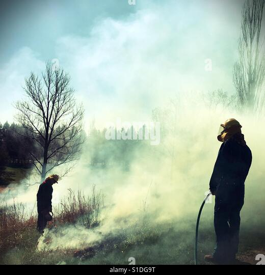 Two people conducting a controlled burn of a field in Minnesota, USA. - Stock Image