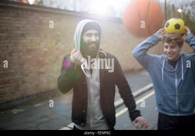 Two men walking in street, holding football - Stock Image