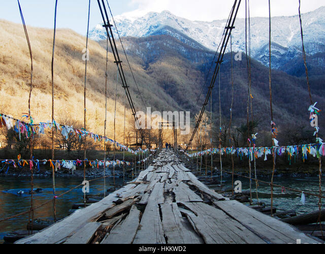 Old wooden bridge hanging over a gorge and mountain stream. Beautiful mountain landscape - Stock Image
