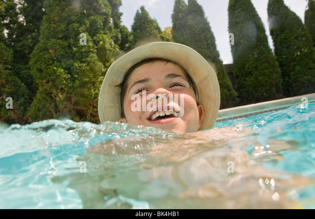 Boy wearing hat in swimming pool - Stock Image