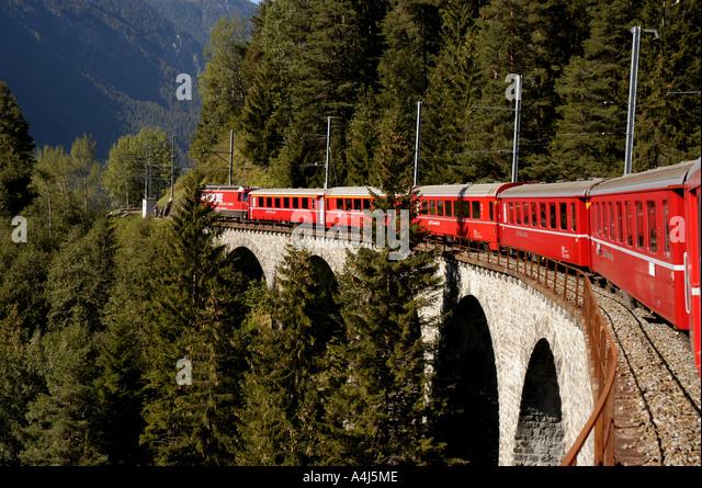 Switzerland red train crossing bridge - Stock Image