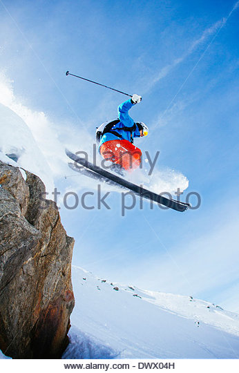 Low angle view of mid adult man skiing against sky - Stock Image