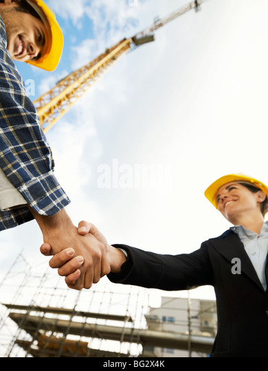 female architect and construction worker shaking hands. Low angle view, copy space - Stock-Bilder