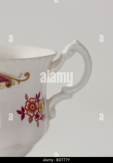 studio shot of delicate white cup with flower pattern on it - Stock Image