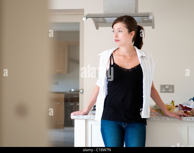 Women deep in thought in kitchen - Stock Image