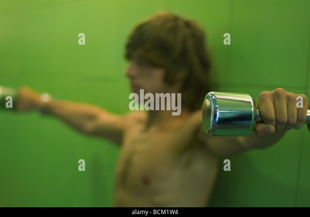 Young man holding dumbbells out to side, side view, focus on foreground - Stock Image