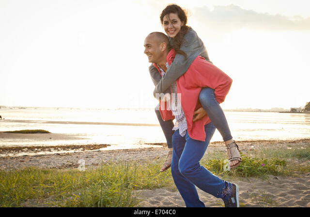 Man giving piggyback ride to woman on beach - Stock Image