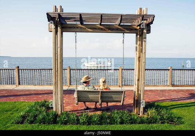 Point Clear Alabama Grand Hotel Marriott Resort hotel lodging Mobile Bay swing love seat fishing boats man woman - Stock Image