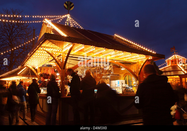 People meet around an illuminated stall at the Christmas Market (Weihnachtsmarkt) in Stuttgart, Germany. - Stock Image