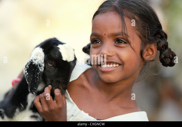 Indian school girl playing with her pet goat Andhra Pradesh South India - Stock-Bilder